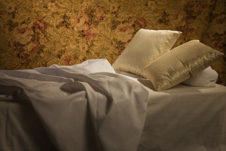 Messy luxurious bed with pillow and quilt cover    photo