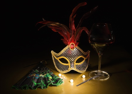 Accessories for the masquerade. Venetian mask, a glass of red wine, boa Stock Photo - 9125625