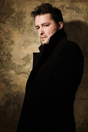 Portrait of a man in black on a sharpened wall background