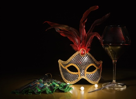 venetian mask: Accessories for the masquerade. Venetian mask, a glass of red wine, boa