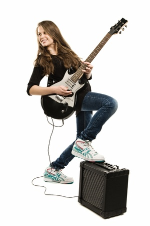 Teenager girl playing guitar against white background photo