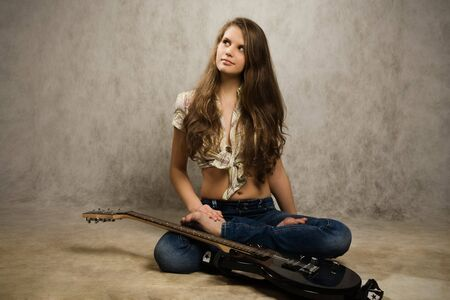 Barefooted teenager girl with electric guitar against gray background photo