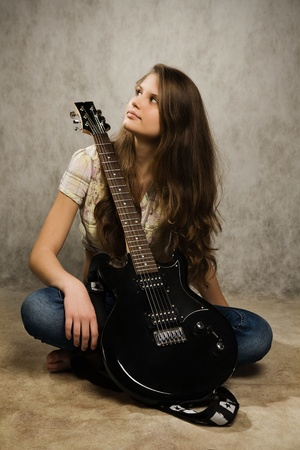 Barefooted teenager  girl with electric guitar against gray background