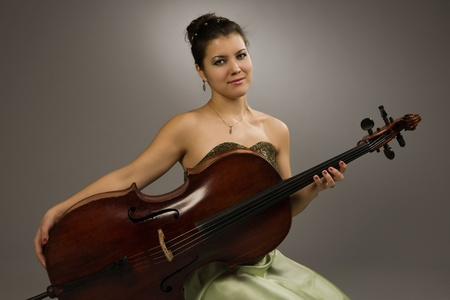 Attractive woman in evening dress with cello photo