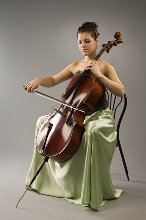 Attractive woman in evening dress playing cello photo