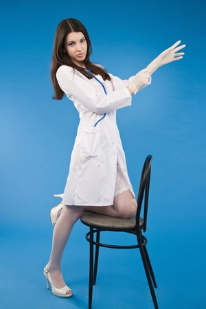 A young sexy nurse pulls medical gloves