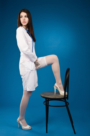 A pretty young nurse straightens stockings on a blue background photo