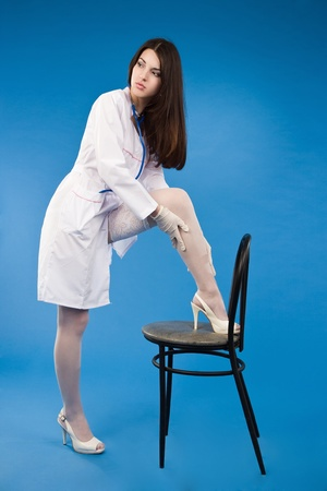A pretty young nurse straightens stockings on a blue background Stock Photo - 9137619