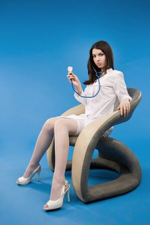 A pretty young nurse with a stethoscope sitting in a chair photo