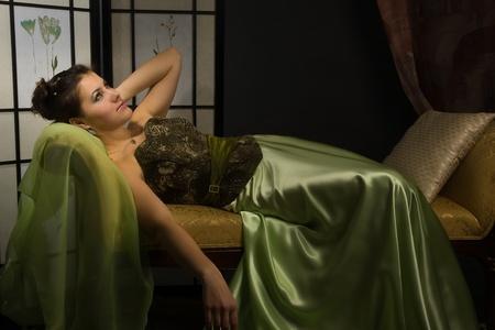 Elegant lady lying on the sofa  in a boudoir photo