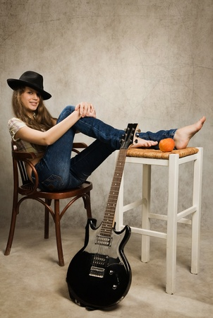 jeans girl: Barefooted teenager girl with electric guitar and apple