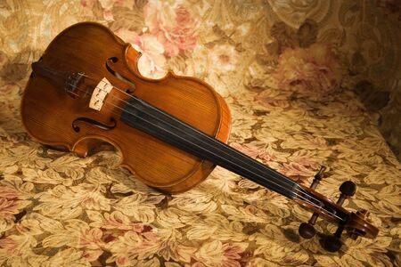 Picture of the old italian violin on a fabric drapes photo