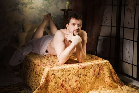 Naked man lying on a couch in the bedroom