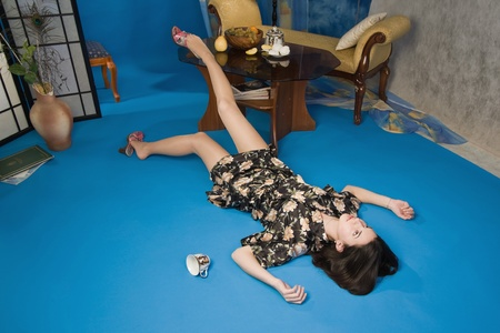 Poisoned brunette in a dressing gown lying on the floor photo