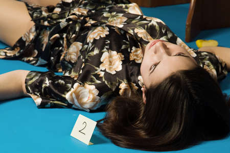 Lifeless brunette in a dressing gown lying on the floor Stock Photo - 9201878