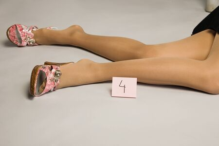 Crime scene. Legs of the lifeless woman. photo