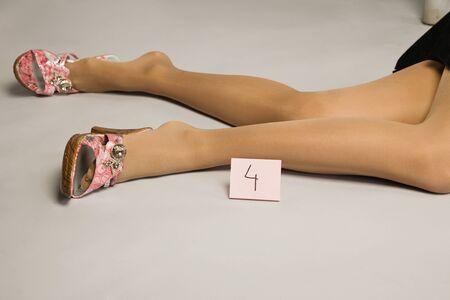 murder: Crime scene. Legs of the lifeless woman.