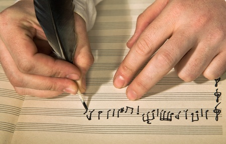 hand written: The hand writes musical notes a feather Stock Photo