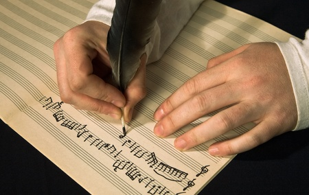 The hand writes musical notes a feather 版權商用圖片