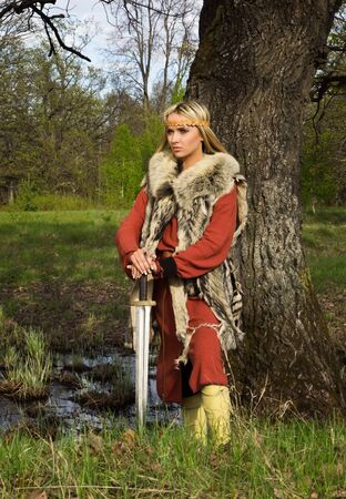 Portrait of the blonde girl in the Scandinavian suit with sword Stock Photo - 9780894