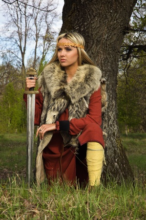 Portrait of the blonde girl in the Scandinavian suit with sword Stock Photo - 9780901