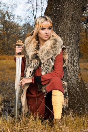 Portrait of the blonde girl in the Scandinavian suit with sword Banque d'images