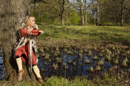 Portrait of the blonde girl in the Scandinavian suit with sword Stock Photo