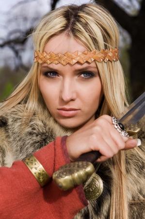 Portrait of the blonde girl in the Scandinavian suit with sword Standard-Bild