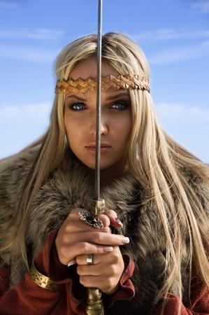 karoling: Portrait of the blonde girl in the Scandinavian suit with sword Stock Photo