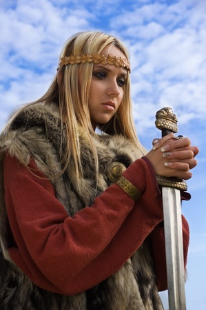 Portrait of the blonde girl in the Scandinavian suit with sword Stock Photo - 9780538