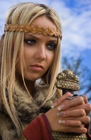 Portret van het blonde meisje in de Scandinavische pak met zwaard