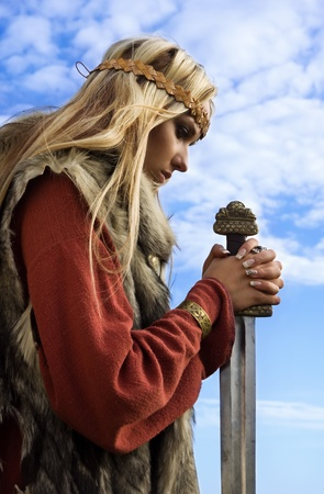 Portrait of the blonde girl in the Scandinavian suit with sword Stock Photo - 9780540