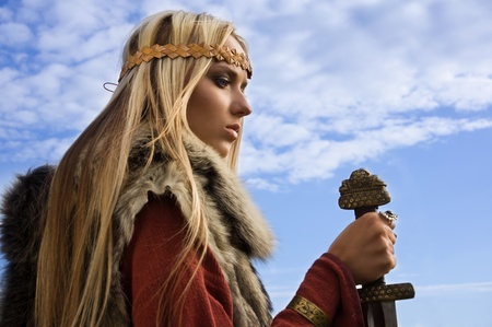Portrait of the blonde girl in the Scandinavian suit with sword Stock Photo - 9780535