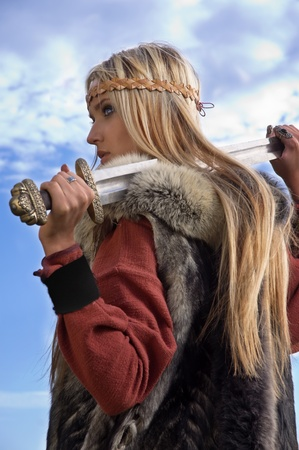 Blonde girl in the Scandinavian suit on a blue sky background Stock Photo