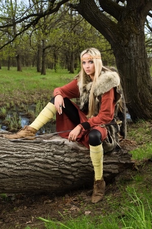Viking girl warrior with sword in a wood Stock Photo - 9780902