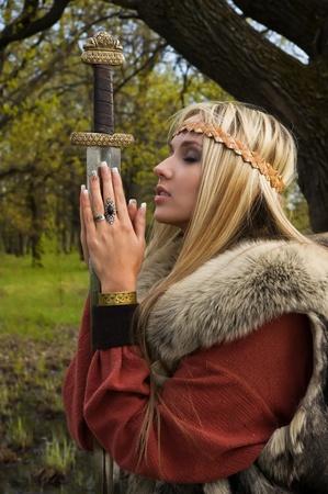 Viking meisje krijger met zwaard in een bos