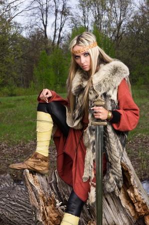 vikingo: Guerrero de chica de vikingo con espada en una madera