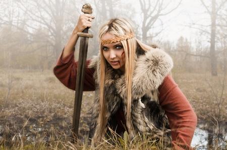 Viking meisje met zwaard in een mist hout Stockfoto