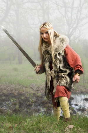 Viking girl warrior with sword in a fight Stock Photo - 9780534
