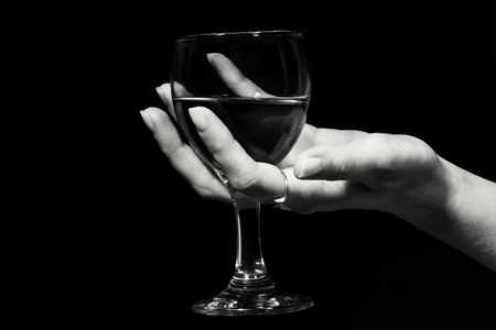 The image of a glass with a red wine in a female hand photo