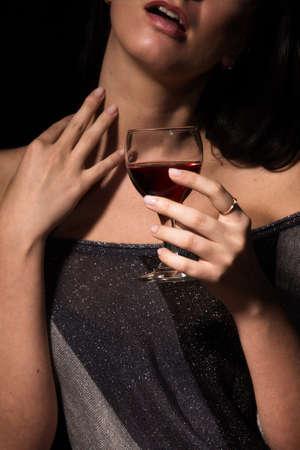 De afbeelding van een glas met een rode wijn in een vrouwelijke kant