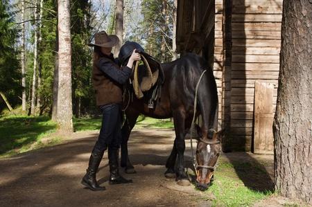 vaqueritas: Joven vaquera en monturas de caballo de sombrero en un rancho Foto de archivo