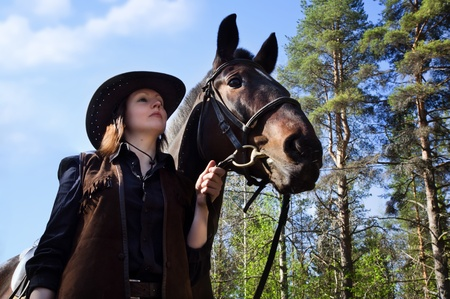 Young cowgirl in hat hugging her horse photo