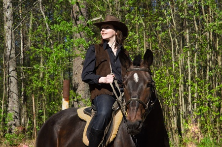Young cowgirl in hat on brown horse  photo