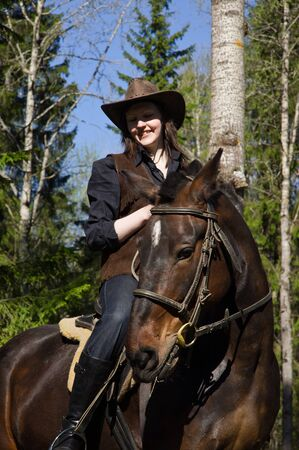 Happy cowgirl in hat on brown horse photo