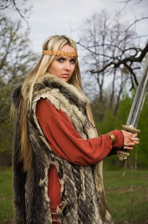 Portrait of the blonde girl in the Scandinavian suit with sword Stock Photo - 9780925