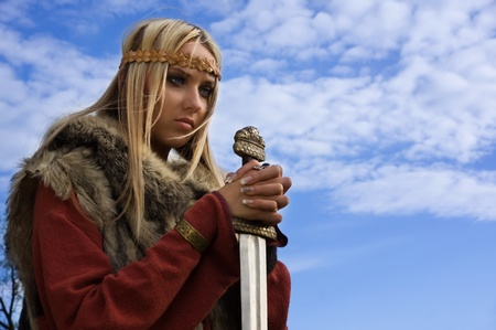 Portrait of the blonde girl in the Scandinavian suit with sword photo