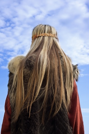 karoling: Blonde girl in the Scandinavian suit on a blue sky background Stock Photo