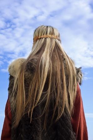 scandinavian girl: Blonde girl in the Scandinavian suit on a blue sky background Stock Photo