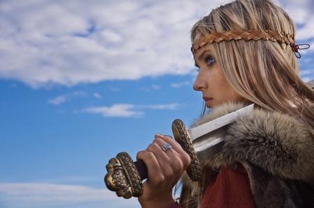 Blond meisje in de Scandinavische pak op een blauwe hemel achtergrond